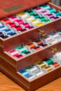 Sewing thread multi colored spools of in a decorative wooden box Stock Photos