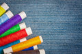 Sewing thread reels on denim Royalty Free Stock Photography