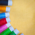 Sewing thread reels on a yellow fabric Royalty Free Stock Photos
