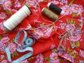 Sewing tools: colored sewing threads, centimeter ribbons and colored pins on a red background close-upвц