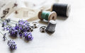 Sewing tools with fresh lavander flowers on linen background. Vintage wooden spool, braid, thimble, buttons. Royalty Free Stock Photo