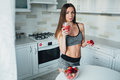 Sexual sports girl holding a bowl of strawberries and a glass of smoothie in the kitchen. Royalty Free Stock Photo
