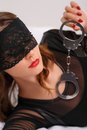 Sexual woman in eye cover holding handcuffs Royalty Free Stock Photo