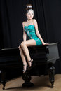 Sexual woman in short mini blue dress sitting on the piano Royalty Free Stock Photography