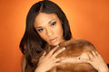 Sexy african american fashion model wearing fur curvy a vintage s fox stole on orange background Royalty Free Stock Images