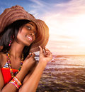 Sexy african woman on the beach closeup portrait of beautiful model posing seashore sunset wearing stylish hat and Royalty Free Stock Image