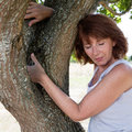 Sexy aging woman touching a tree for wellbeing senior green wellness radiant mature in harmony with nature seeking serenity and Royalty Free Stock Photography