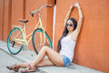 Sexy asian woman sitting near the wall and vintage bicycle Royalty Free Stock Photo