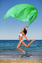 Sexy athletic brunette jumping on the beach with a large green cloth Royalty Free Stock Photo
