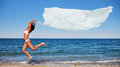 Sexy athletic brunette jumping on the beach with a large white cloth horizontal frame Stock Photography