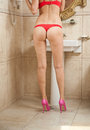 Sexy beautiful body shoot of young woman wearing red lingerie and high heels in bathroom woman body with long legs front the Royalty Free Stock Images
