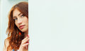 Sexy beautiful girl with red hair and full lips peeping from behind the white wall Royalty Free Stock Photo