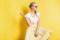 Sexy beautiful woman in skirt and sunglasses with lollipop on yellow background Royalty Free Stock Image