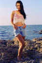 Sexy beautiful woman wears a top with jeans shorts and posing beach Royalty Free Stock Photo