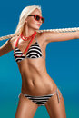 Sexy bikini model holding on the rope Royalty Free Stock Images