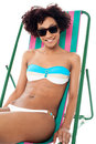 Sexy bikini model seated on a deckchair Royalty Free Stock Photo