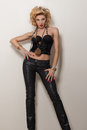 Sexy blond adult woman in black corset and trousers posing over white background Stock Photos