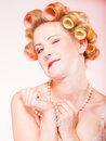 Sexy blond girl with curlers in underwear and beads having fun making funny face young woman on pink preparation for party Royalty Free Stock Photos