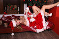 Sexy blond girl in Santa costume posing with Christmas presents Royalty Free Stock Photo