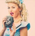 Sexy blond pin up woman coquette style young in blue dress with vintage camera Royalty Free Stock Photography