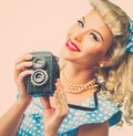Sexy blond pin up woman coquette style young in blue dress with vintage camera Stock Photo