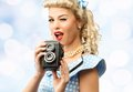 Sexy blond pin up young woman coquette style in blue dress with vintage camera Royalty Free Stock Photo