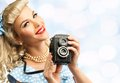 Sexy blond pin up young woman coquette style in blue dress with vintage camera Royalty Free Stock Image