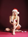 A sexy blond sitting in erotic Christmas lingerie Stock Photos