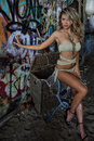 Sexy blond swimsuit model wearing bikini and jewelry posing pretty in front of graffiti background with marine style accessories Royalty Free Stock Images