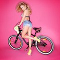 Sexy blond woman with a bicycle leggy shapely in trendy denim shorts and high heels posing on pink studio background Stock Image