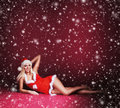 A sexy blond woman in erotic santa lingerie on the snow young and caucasian laying image is taken red background with falling Royalty Free Stock Image