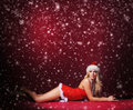 A sexy blond woman in erotic santa lingerie on the snow young and caucasian laying image is taken red background with falling Royalty Free Stock Photos