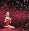 A sexy blond woman in erotic santa lingerie on the snow young and caucasian posing image is taken red background with falling Stock Photo