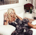 Sexy blond woman in lingerie and fur coat lying on bed with champagne Royalty Free Stock Photo