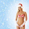 A sexy blond woman posing in erotic santa lingerie young and caucasian the image is taken on light blue snowy background Stock Photos