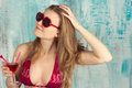 Sexy blond woman with sunglasses and pink swimsuit taking pose playing pareo Royalty Free Stock Photo