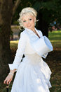 Sexy blonde bride in the park with a cane and a hat cylinder Stock Image