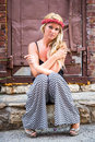 Sexy blonde girl in casual fashion woman with black and white clothing and red rose headband sitting urban alley with red brick Stock Photo