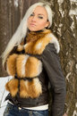 Sexy blonde girl lean on a tree winter Royalty Free Stock Photos
