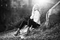 Sexy blonde girl sitting near big rock on top of mountain black and white photo Stock Photo