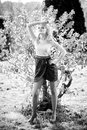 Sexy blonde girl standing near lonely small tree black and white portrait of Stock Photo