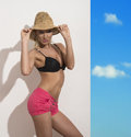 Sexy blonde girl straw hat black bra pink shorts looks to lens touches hat both hands Royalty Free Stock Photo