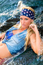 Sexy blonde girl in swimsuit woman fashion model sitting with legs extended flowing water wearing bandana on head long hair and Stock Images