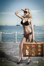 Sexy blonde tourist with vintage bag woman bikini taking old fashion suitcase in the hand and searching something her look on a Stock Images