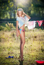 Sexy blonde woman in bikini putting clothes to dry in sun sensual fair hair young female on high heels outdoor out the washing Stock Photo