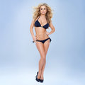 Sexy blonde woman black bikini gray background Royalty Free Stock Photography