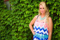 Sexy blonde woman in casual fashion on ivy wall girl with long hair and sun dress standing against a covered green Royalty Free Stock Photo