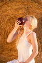 Sexy blonde woman drinking milk on hay background Stock Photo