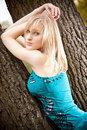 Sexy blonde woman leaning against tree at park closeup portrait of Stock Images