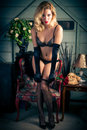 Sexy blonde woman in lingerie a young attractive blond poses provocatively and seductively wearing fishnet stockings and black bra Stock Photos